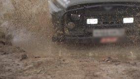 Ακραίες συνθήκες οδήγησης στην επαρχία Κινήσεις ενός ισχυρές SUV σε μια βαθιά λακκούβα Πετώντας παφλασμοί και ρύπος φιλμ μικρού μήκους