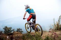 Ακραίος αθλητής κοριτσιών στο ποδήλατο στην κορυφή του βουνού στοκ φωτογραφίες