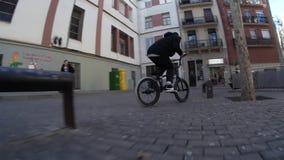 Ακραίος ποδηλάτης BMX που κάνει τις διαφορετικά περιστροφές και τα τεχνάσματα στο ποδήλατο στο αστικό περιβάλλον απόθεμα βίντεο