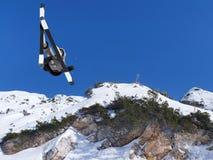 Ακραίος σκιέρ που πηδά από τον ουρανό βουνών στο backgraund στοκ εικόνες