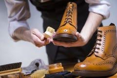 Ακραίος στενός επάνω επανδρώνει τα χέρια που καθαρίζουν τα ξοντρά παπούτσεις δέρματος μόσχων πολυτέλειας με τα ειδικά εξαρτήματα Στοκ Φωτογραφίες