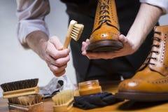 Ακραίος στενός επάνω επανδρώνει τα χέρια που καθαρίζουν τα ξοντρά παπούτσεις δέρματος μόσχων πολυτέλειας Στοκ φωτογραφία με δικαίωμα ελεύθερης χρήσης
