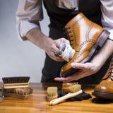 Ακραίος στενός επάνω επανδρώνει τα χέρια που καθαρίζουν τα ξοντρά παπούτσεις δέρματος μόσχων πολυτέλειας με το ειδικό ύφασμα Στοκ Εικόνα