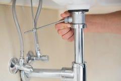 Ακραίος στενός επάνω του χεριού ενός υδραυλικού και washbasin του αγωγού Στοκ εικόνα με δικαίωμα ελεύθερης χρήσης