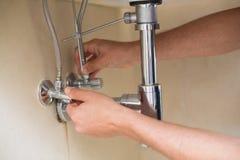 Ακραίος στενός επάνω των χεριών ενός υδραυλικού και washbasin του αγωγού Στοκ Εικόνες
