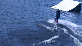 Ακραίο άτομο που μελετά τη wakeboarding ακροβατική επίδειξη οδήγησης στο νερό Ακραίος αθλητισμός νερού απόθεμα βίντεο