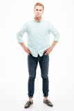 0 ακριβής νεαρός άνδρας που στέκεται με τα χέρια στα ισχία Στοκ Φωτογραφίες