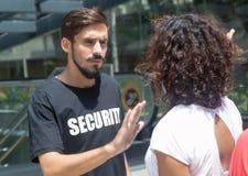 Ακριβής φρουρά ασφάλειας με τους φιλοξενουμένους στην είσοδο στοκ εικόνα με δικαίωμα ελεύθερης χρήσης