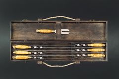 Κλείστε επάνω τα μεγάλα οβελίδια ανοξείδωτου πολυτέλειας λαβών που τίθενται στο ξύλινο κιβώτιο για τη σχάρα και τη σχάρα Ακριβός  στοκ φωτογραφίες