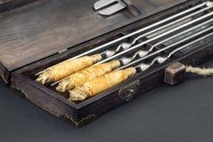 Κλείστε επάνω τα μεγάλα οβελίδια ανοξείδωτου πολυτέλειας λαβών που τίθενται στο ξύλινο κιβώτιο για τη σχάρα και τη σχάρα Ακριβός  στοκ εικόνα