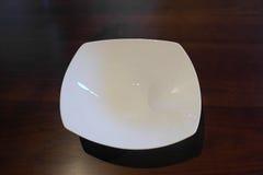 Ακριβό τετραγωνικό διαμορφωμένο πιάτο πορσελάνης πολυτέλειας σε μια δρύινη επιτραπέζια ρύθμιση Στοκ εικόνες με δικαίωμα ελεύθερης χρήσης