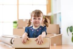 Ακριβώς κινημένος σε ένα νέο σπίτι Το παιδί κάθεται μέσα στο κιβώτιο στοκ εικόνες