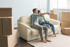Ακριβώς κινημένο νέο ζεύγος στο εσωτερικό προγραμματισμού καναπέδων σε ένα καινούργιο σπίτι Στοκ φωτογραφία με δικαίωμα ελεύθερης χρήσης