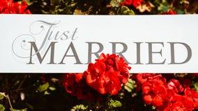 Ακριβώς παντρεμένο κείμενο στο άσπρο υπόβαθρο με τα λουλούδια Στοκ φωτογραφία με δικαίωμα ελεύθερης χρήσης