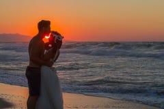 Ακριβώς παντρεμένο νέο ζευγάρι σε μια μουντή παραλία στο σούρουπο Στοκ Εικόνες