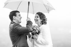 Ακριβώς το παντρεμένο ζευγάρι έχει τη διασκέδαση κάτω από την ομπρέλα Στοκ Εικόνα