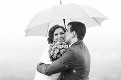 Ακριβώς το παντρεμένο ζευγάρι έχει τη διασκέδαση κάτω από την ομπρέλα Στοκ εικόνες με δικαίωμα ελεύθερης χρήσης