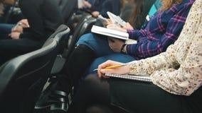 Ακροατές που συμμετέχουν σε μια διάλεξη - άνθρωποι που γράφουν στα σημειωματάριά τους απόθεμα βίντεο