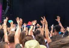 Ακροατήριο με τα χέρια που αυξάνονται σε ένα φεστιβάλ μουσικής, κενή σκηνή με το διάστημα αντιγράφων στοκ εικόνες