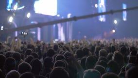 Ακροατήριο συναυλίας με τα χέρια επάνω και τα φωτεινά φω'τα σκηνών φιλμ μικρού μήκους