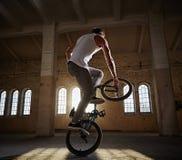 Ακροβατική επίδειξη BMX και οδήγηση άλματος σε μια αίθουσα με το φως του ήλιου Στοκ Εικόνα