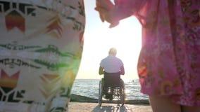 Ακρωτηριάστε στην αναπηρική καρέκλα με την οικογένεια, η μητέρα και η κόρη κρατούν τα χέρια στη συνεδρίαση πατέρων υποβάθρου στις απόθεμα βίντεο