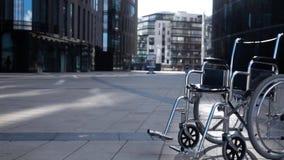 Ακρωτηριάστε την αναπηρική καρέκλα που κυλά κοντά στο σύγχρονο κτήριο απόθεμα βίντεο