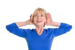 Ακρόαση ηλικιωμένων γυναικών που απομονώνεται στο άσπρο υπόβαθρο στοκ φωτογραφία με δικαίωμα ελεύθερης χρήσης
