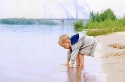 ακτή αγοριών κοντά στον ποταμό φυτών Στοκ εικόνες με δικαίωμα ελεύθερης χρήσης