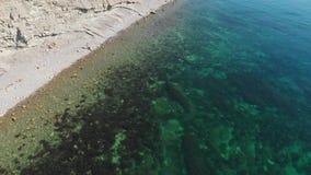 Ακτή θάλασσας με την παραλία πετρών και σαφές μπλε νερό από τον κηφήνα Τοπ όψη εναέρια όψη φιλμ μικρού μήκους