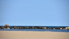 Ακτή με την άμμο, το νερό, τους βράχους και το μπλε ουρανό Στοκ Εικόνες