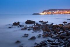 Ακτή με τις πέτρες και φω'τα στο υπόβαθρο Στοκ φωτογραφία με δικαίωμα ελεύθερης χρήσης