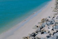 Ακτή με το μπλε θαλάσσιο νερό και πέτρινος στην παραλία στοκ φωτογραφία με δικαίωμα ελεύθερης χρήσης