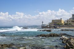 Ακτή στο ελαστικό αυτοκινήτου στον ωκεανό με τα κύματα και με το φάρο στο ελαστικό αυτοκινήτου, ξινό, Λίβανος στοκ εικόνες