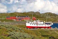 Ακτή της λίμνης Bygdin με τη βάρκα και τα παραδοσιακά νορβηγικά κτήρια Στοκ Εικόνες
