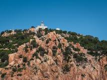 Ακτή της Σαρδηνίας: Άσπρος πύργος φάρων στους βράχους και τους απότομους βράχους ν Στοκ φωτογραφία με δικαίωμα ελεύθερης χρήσης