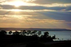 Ακτίνες ήλιων που λάμπουν μέσω των σύννεφων στη λίμνη Wilson Στοκ Φωτογραφίες