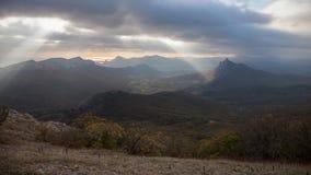 Ακτίνες ήλιων μέσω των σύννεφων που επιπλέουν πέρα από τα βουνά απόθεμα βίντεο