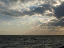 Ακτίνες ήλιων που προεξέχουν μέσω των σύννεφων και επάνω στη θάλασσα Στοκ Εικόνες