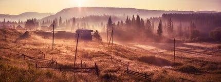 Ακτίνες ήλιων πρωινού στο σπίτι βουνών ομίχλης Στοκ φωτογραφία με δικαίωμα ελεύθερης χρήσης