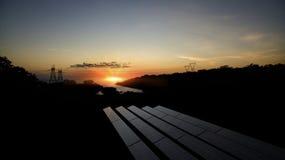 Ακτίνες ηλιοβασιλέματος πέρα από φωτοβολταϊκές εγκαταστάσεις παραγωγής ενέργειας Στοκ Εικόνες