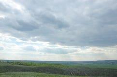 Ακτίνες του ήλιου από πίσω από μια κάλυψη σύννεφων τα λιβάδια και οι τομείς Στοκ Εικόνες