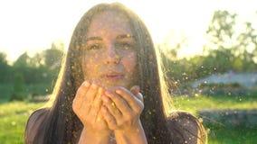 Ακτινοβολήστε γυναίκα Όμορφο φυσώντας κομφετί γυναικών σε σε αργή κίνηση υπαίθρια Το καυκάσιο ευτυχές έφηβη με το χρυσό ακτινοβολ φιλμ μικρού μήκους