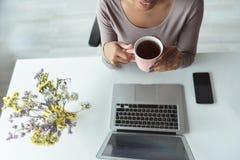 Ακτινοβολία του δοκιμάζοντας ποτού γυναικών στο γραφείο Στοκ εικόνες με δικαίωμα ελεύθερης χρήσης