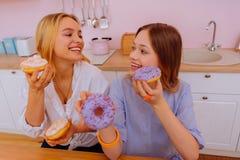 Ακτινοβολώντας αδελφές που έχουν μερικά γλυκά doughnuts για το πρόγευμα στοκ εικόνες με δικαίωμα ελεύθερης χρήσης