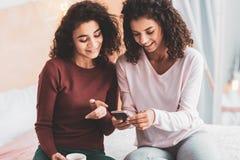 Ακτινοβολώντας κορίτσια που αισθάνονται τις ευτυχείς φωτογραφίες προσοχής στο τηλέφωνο στοκ εικόνες