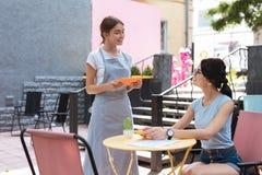 Ακτινοβολώντας πελάτης του εστιατορίου που απολαμβάνει την επικοινωνία με τη σερβιτόρα στοκ εικόνες