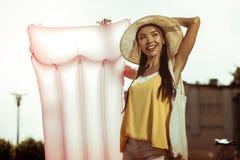 Ακτινοβόλος γυναίκα που φορά το καπέλο που κρατά ένα ρόδινο διογκώσιμο στρώμα αέρα στοκ φωτογραφία με δικαίωμα ελεύθερης χρήσης