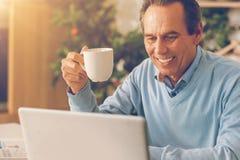 Ακτινοβόλο άτομο που πίνει τον καφέ του και που χρησιμοποιεί το lap-top στο σπίτι Στοκ Εικόνα