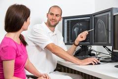 Ακτινολόγος που ένας ασθενής που χρησιμοποιεί τις εικόνες από tomograpy ή MRI Στοκ εικόνα με δικαίωμα ελεύθερης χρήσης
